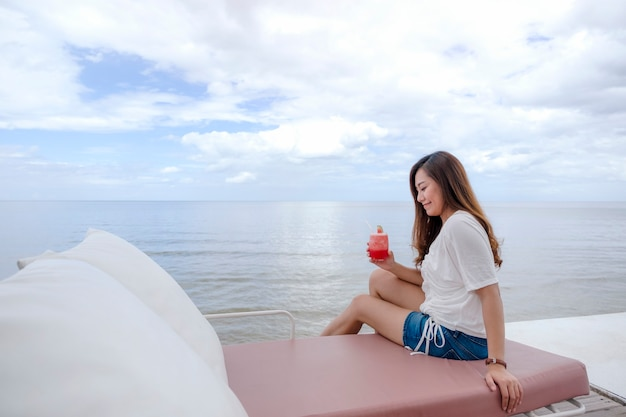 A beautiful asian woman drinking watermelon juice while sitting by the sea