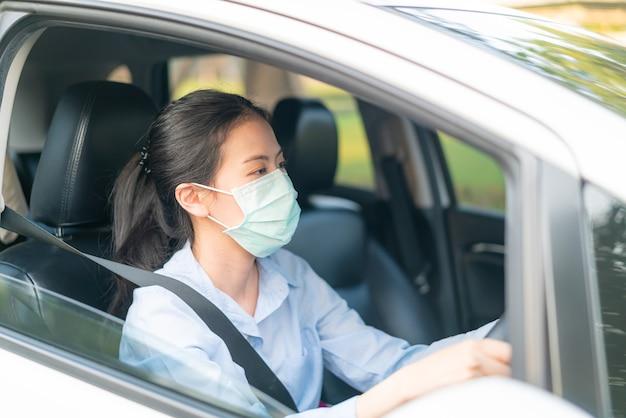 밖에 나가는 안면 마스크를 쓰고 차를 운전하는 아름다운 아시아 여성은 코로나 바이러스 covid-19 바이러스 감염 질병 발발 세계 대유행, 교통 대기 오염 방출로부터 건강을 보호합니다.