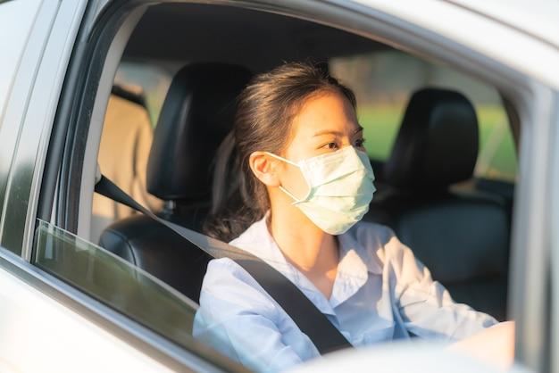 外に出るフェイスマスクを身に着けている車を運転している美しいアジアの女性は、コロナウイルスcovid-19ウイルス感染症の発生から世界的大流行、交通大気汚染の排出から健康を維持します