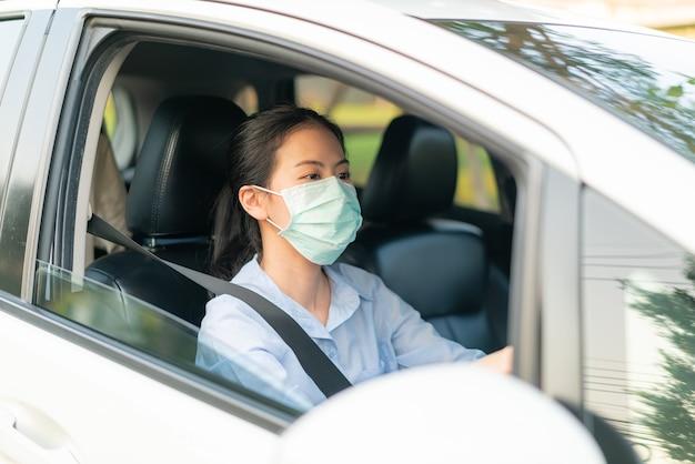 外に出るフェイスマスクを身に着けている車を運転している美しいアジアの女性は、コロナウイルスcovid-19ウイルス感染症の発生世界大流行、交通大気汚染の排出から健康を維持します