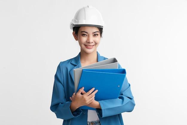 美しいアジアの女性エンジニアと白い背景、建設コンセプト、エンジニア、業界の安全ヘルメット。