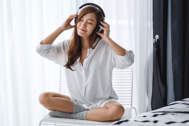 A beautiful asian woman enjoy listening to music with headphone in bedroom , happiness and relaxation concepts
