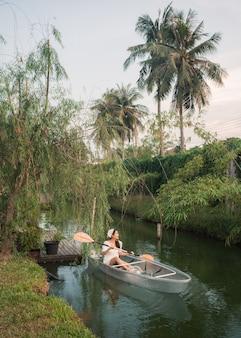 Красивая азиатская женщина наслаждается греблей на прозрачной лодке у канала в тропическом лесу на выходных