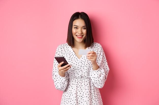 美しいアジアの女性は、携帯電話アプリにクレジットカード情報を入力し、オンラインで買い物をし、スマートフォンで注文の支払いをし、ピンクの上に立っています。