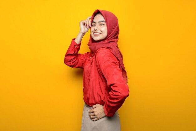 黄色の背景に興奮して美しいアジアの女性