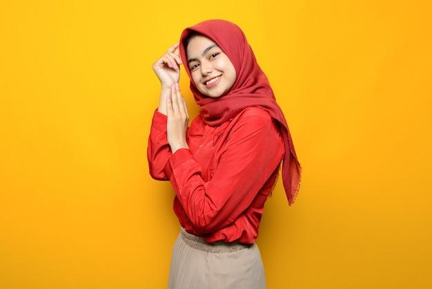 Красивая азиатская женщина взволнована на желтом фоне