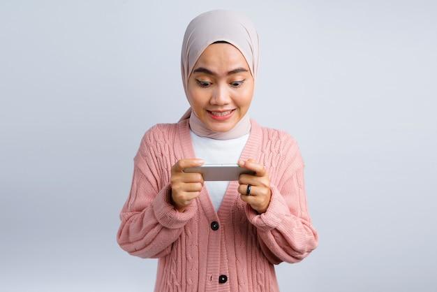 美しいアジアの女性は白とスマートフォンでゲームを興奮して遊ぶ