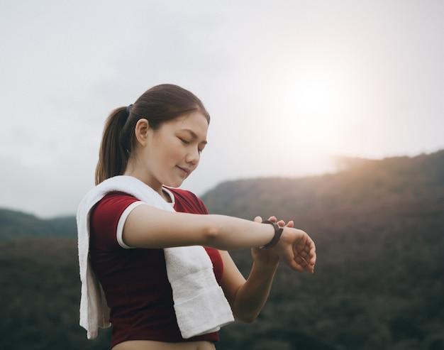 美しいアジアの女性は外で運動し、彼女のスマートな時計に見える