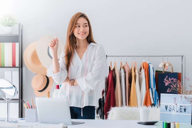 Beautiful asian woman fashion designer standing in the clothing store