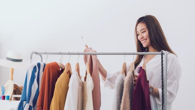 옷가게에 서있는 아름 다운 아시아 여자 패션 디자이너