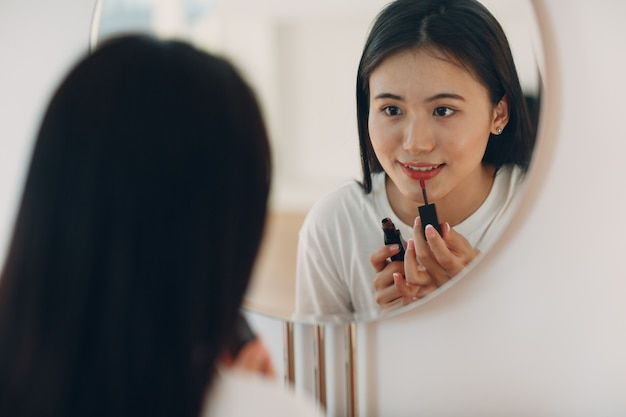 Beautiful asian woman front of mirror applying make up lips with lipstick at living room
