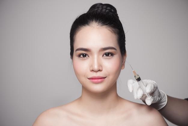 美しいアジアの女性は、美しさの顔の注射を取得します。顔の老化注射。