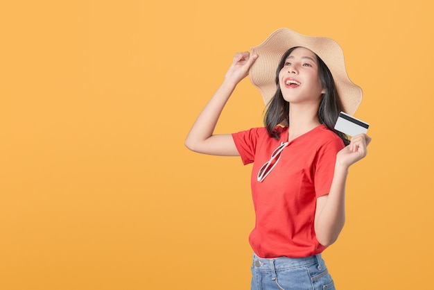 Beautiful asian woman good skin wearing hat  holding credit card payment on orange background.