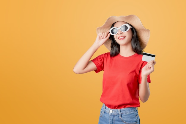 Beautiful asian woman good skin, wearing sunglasses posing holding credit card payment on orange .