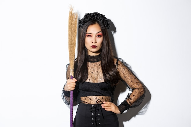 Beautiful asian woman in gothic lace dress and black wreath, holding broom and looking suspicious