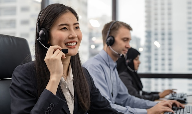 Beautiful asian woman and group of diverse telemarketing customer service staff team in call center. call center worker accompanied by team. smiling of customer support operator at work.