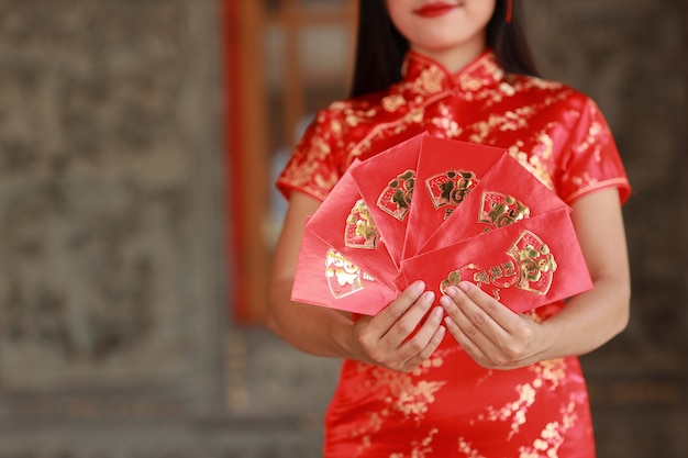 Красивая азиатская женщина руки в красном китайском платье традиционного чонсам ципао с жестом показа красного конверта или любого пао, текст означает удачу, входящую в дом (китайский новый год)