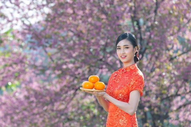Улыбка красивой азиатской женщины счастливая и держа свежие апельсины в китайском новом году на розовом фоне. Бесплатные Фотографии