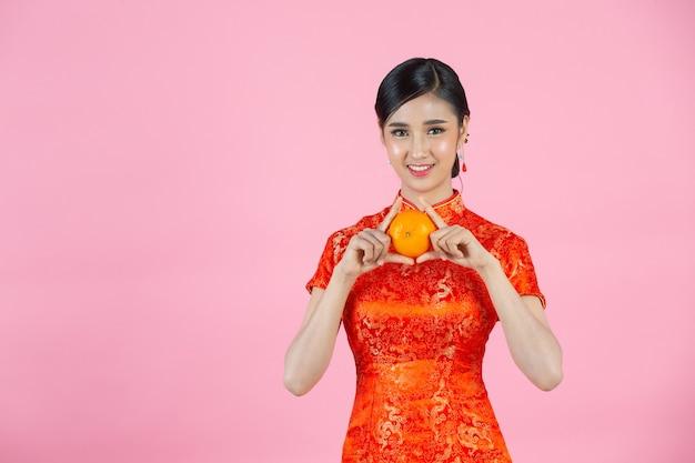 美しいアジアの女性の幸せな笑顔とピンクの背景に中国の旧正月に新鮮なオレンジを保持しています。