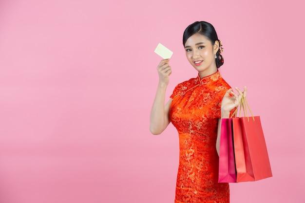 아름 다운 아시아 여자 행복 한 미소와 분홍색 배경에 중국 새 해에 쇼핑.