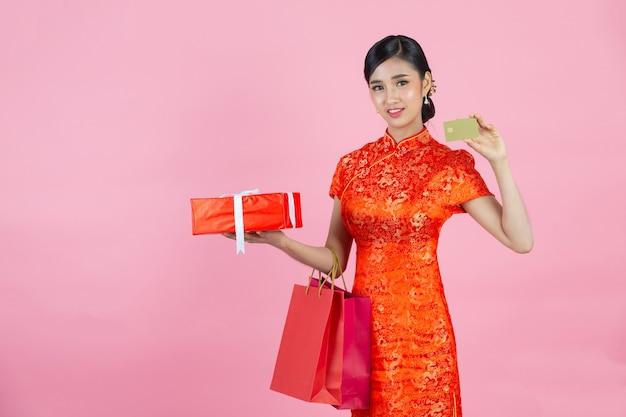 아름 다운 아시아 여자 행복 미소와 분홍색 배경에 중국 새 해에 신용 카드를 표시합니다.