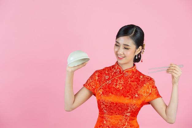 Bella donna asiatica sorriso felice e mangiare nel nuovo anno cinese su sfondo rosa.
