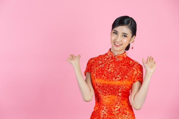 La bella donna asiatica sorride felice e si sente eccitata nel nuovo anno cinese su sfondo rosa.
