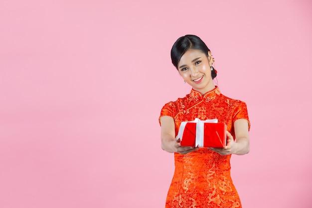 Sorriso felice della bella donna asiatica e contenitore di regalo della tenuta nel nuovo anno cinese su fondo rosa.