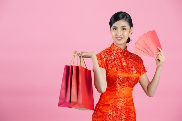 Beautiful asian woman happy smile and shopping in chinese new year on pink background.