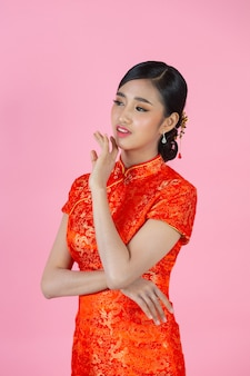 Beautiful asian woman happy smile and show something to you in chinese new year on pink background.