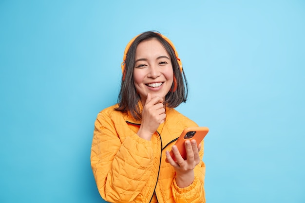 Beautiful asian woman has toothy smile enjoys listening great song from her playlist uses modern smartphone wireless stereo headphones holds chin wears orange jacket isolared over blue wall.