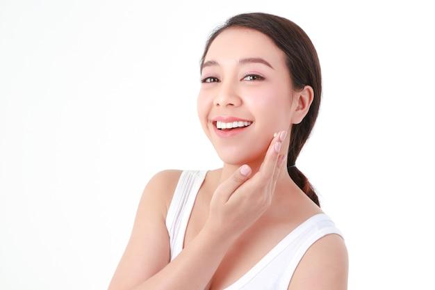 美しいアジアの女性美しい笑顔、きれいな白い歯を持っています。スキンクリームで顔の健康に気をつけましょう。美容コンセプト。白色の背景
