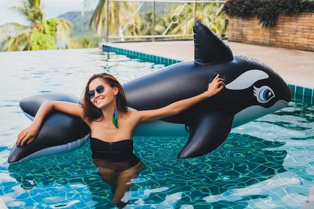 タイの夏休みにトロピカルヴィラのプールで楽しんでいる美しいアジアの女性は、大きなシャチを着て黒い水着とサングラス、セクシーなボディ、ファッションアクセサリーで遊んでいます