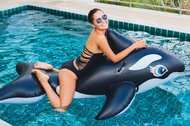 Beautiful asian woman having fun in pool on tropical villa on summer vacation in thailand playing with big orca wearinng black swimsuit and sunglasses, sexy body, fashion accessories