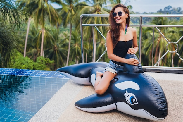 Beautiful asian woman having fun at pool on tropical villa on summer vacation in thailand playing with big orca wearinng black swimsuit and sunglasses, sexy body, positive showing thumbs up
