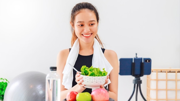 Beautiful asian woman healthy blogger is showing apple fruit and clean diet food. in front of the smartphone to recording vlog video live streaming at home.