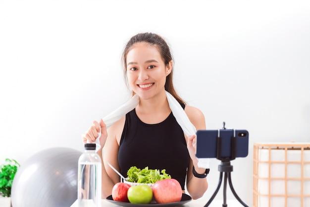 아름 다운 아시아 여자 건강 블로거 사과 fruite와 깨끗 한 다이어트 음식을 보이고있다.