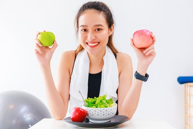 Beautiful asian woman healthy blogger is showing fruit and clean diet food in front of the camera to recording vlog video live streaming at home.