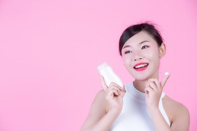 분홍색 배경에 제품의 병을 들고 아름 다운 아시아 여자.