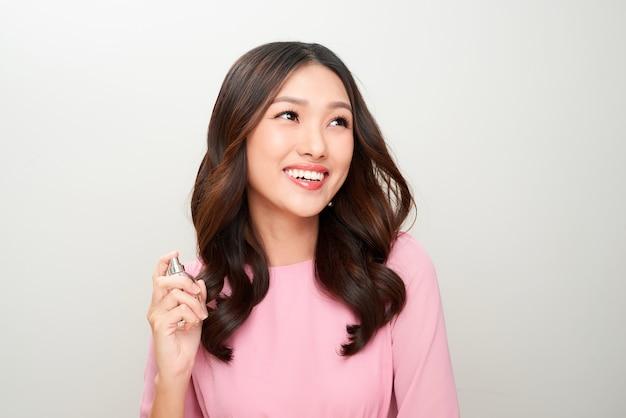 香水瓶を持ってそれを適用する美しいアジアの女性
