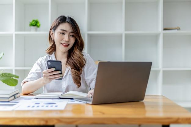 스마트폰을 들고 노트북을 사용하는 아름다운 아시아 여성, 여성 사업가가 노트북으로 파트너와 함께 회의 일정을 잡고 채팅을 하고 있습니다. 의사 소통을 위해 기술을 사용하는 개념.