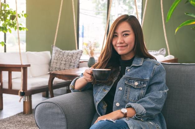 Красивая азиатская женщина держа и выпивая горячий кофе в кафе