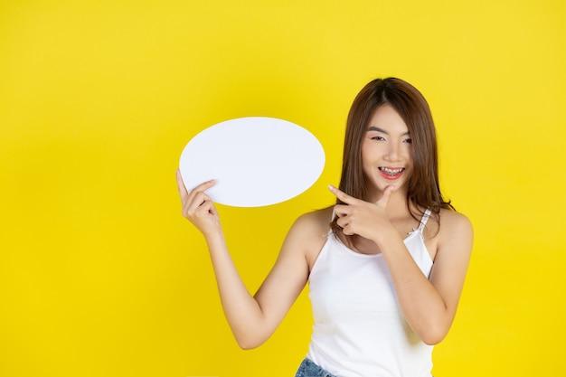 Красивая азиатская женщина, держащая и глядя на речевой пузырь с пустым пространством