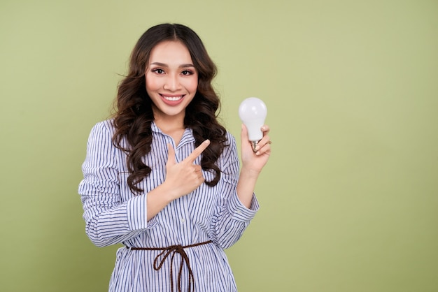 Красивая азиатская женщина держа и указывая электрическую лампочку
