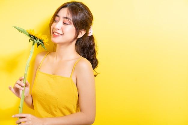 아름 다운 아시아 여자를 노란색에 해바라기와 함께 포즈