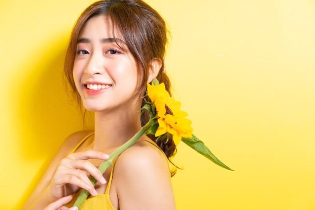 黄色のひまわりを持ってポーズをとって美しいアジアの女性