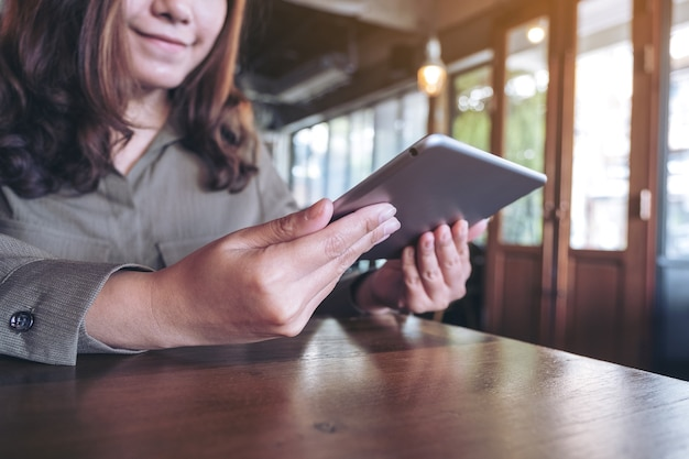 아름 다운 아시아 여자를 카페에서 태블릿 pc를 사용 하여