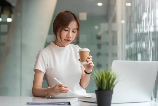 Красивая азиатская женщина держа кружку кофе сидя работая компьтер-книжку в современном офисе.