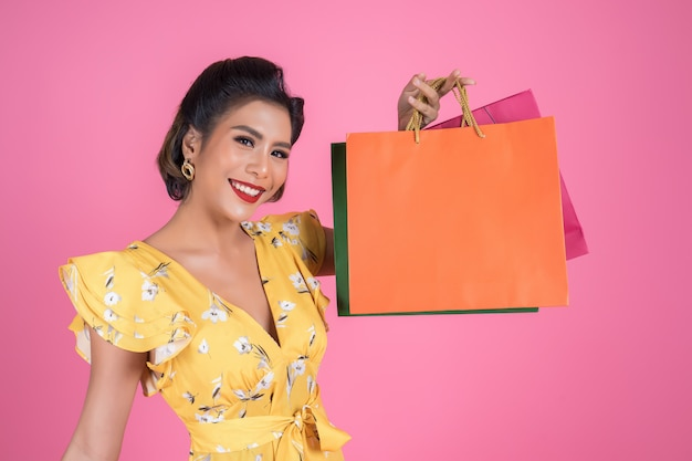 Beautiful asian woman holding colored shopping bags