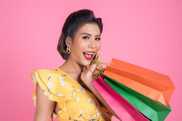 Beautiful asian woman holding colored shopping bags